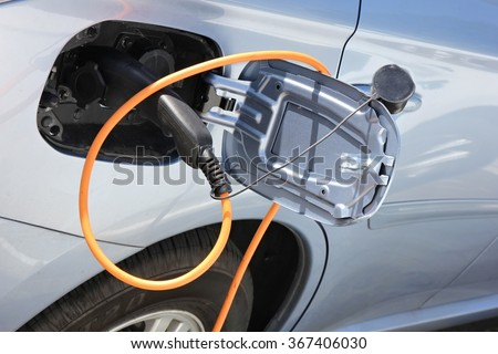 hybrid car being charged - stock photo