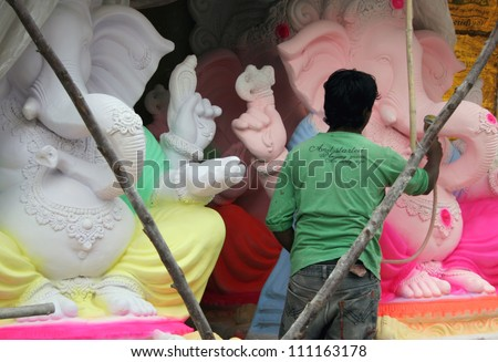 HYDERABAD,AP,INDIA- AUGUST 25:Artists making the ganesha idol for the hindu festival ganesha chathurthi on August 25,2012 in Hyderabad,India.Thousands of Idols in different sizes are made every year. - stock photo