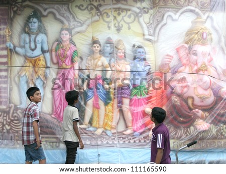 HYDERABAD,AP,INDIA-AUGUST 25:Children  looking at the Ganesh idol kept for sale during  hindu festival ganesh chathurthi on August25,2012 in Hyderabad,India.Thousands of idols are made every year. - stock photo