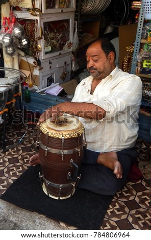HYDERABAD,INDIA-DECEMBER 30 :Indian man repair traditional drums in a shop in the market place  on December 30,2017 in Hyderabad,India.