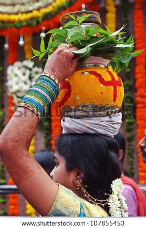 HYDERABAD, INDIA - JULY 15: An unidentified Hindu lady carries a decorated pot and visits a temple to celebrate famous Bonalu festival during monsoon on July 15, 2012 at Hyderabad, India.