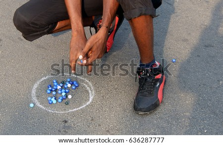 HYDERABAD,INDIA-MAY 7: Indian people play marbles on the road outdoors on physical literacy days Sunday mornings on open roads May 7,2017 in Hyderabad