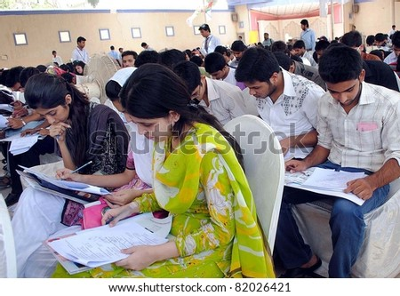 HYDERABAD, PAKISTAN - JUL 31: Students solve papers during pre-entry test for admissions in medical and engineering universities organized by (APMSO) on July 31, 2011 in Hyderabad.