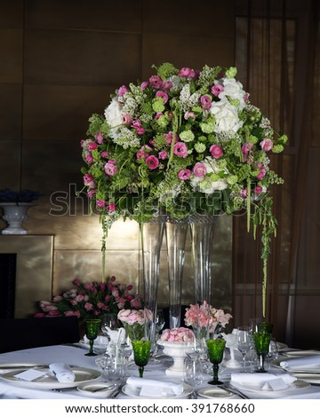 Hydrangea and pink ranunculus Floral Arrangement in Vase as decoration of wedding dinner with green glasses with wine - stock photo
