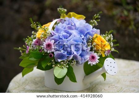 Hydrangea flower arrangement in watering can. Wedding decoration - stock photo