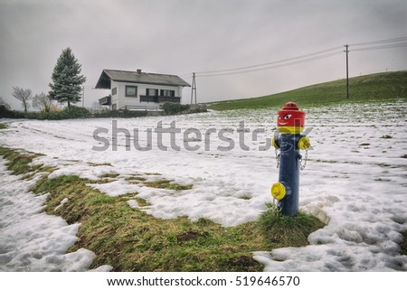 Hydrant painted in the man. Humorously painted hydrant in the snow-covered meadow with house and pine on background