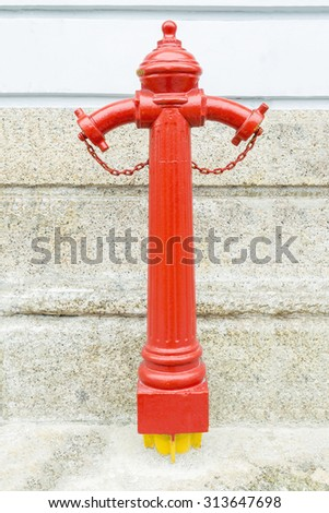 Hydrant used for water injection on stone wall background - stock photo