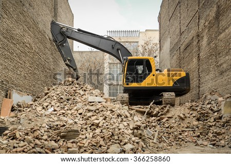 Hydraulic excavator on house construction waste - stock photo
