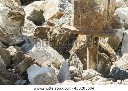 Hydraulic hammer shatters stones - stock photo