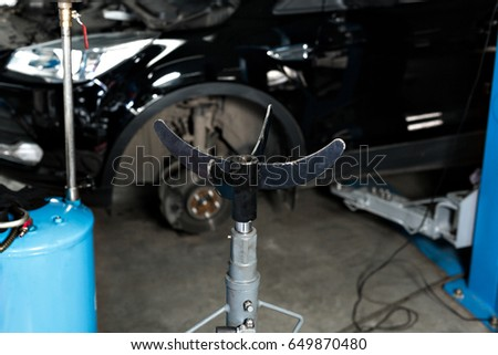 hydraulic Jack for the engine, and large auto parts. The car on the lift prepared to repair