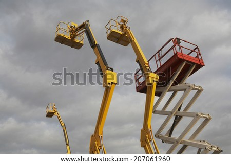 Hydraulic lift machines against stormy sky - stock photo