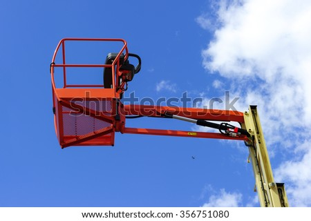 Hydraulic lift platform with bucket of construction vehicle painted in orange and beige colors with white clouds and blue sky on background