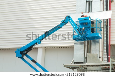 Hydraulic mobile construction platform elevated towards a blue - stock photo