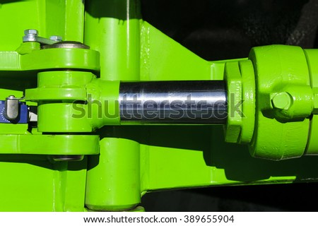 Hydraulic piston system for bulldozers, tractors, excavators, chrome plated cylinder shaft of green machine, construction heavy industry detail, selective focus - stock photo