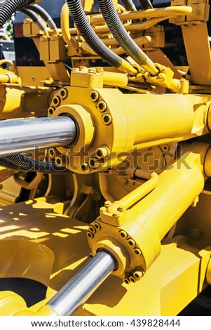 hydraulics tractor yellow. focus on the hydraulic pipes - stock photo