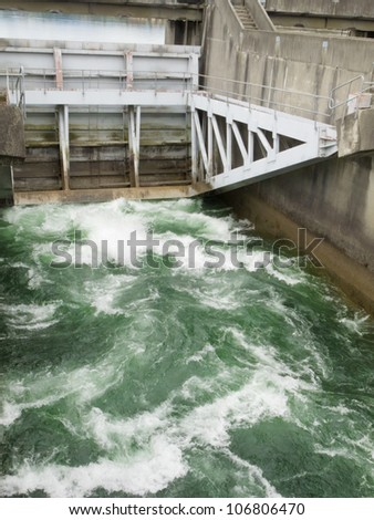 Hydro control structure weir with flow passing underneath causing a violent turbulence discharge of white water - stock photo