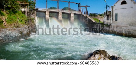 Hydroelectric power plant generates electricity. Construction on the river Chemal, Altay, Russia - stock photo
