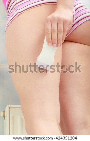 Hygiene skin body care concept. Hair removal. Closeup woman shaving legs with electric shaver depilator in bathroom