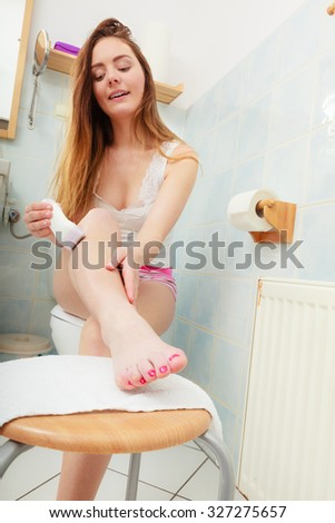 Hygiene skin body care concept. Hair removal. woman shaving legs with electric shaver depilator in bathroom