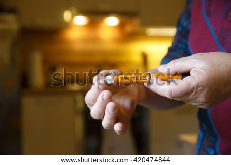 Hyperglycemic diabetic patient opening her insulin shot at home in the kitchen before eating. Medical process, self-diagnose, common metabolic, widespread and modern epidemic disease concept.   