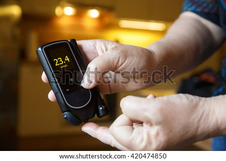 Hyperglycemic diabetic patient testing her blood for sugar level at home; high blood sugar. Medical process, self-diagnose, common metabolic, widespread and modern epidemic disease concept.   