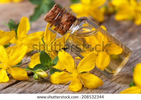 hypericum oil in a glass bottle on the table macro horizontal  - stock photo