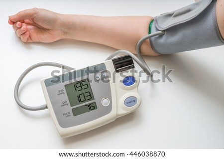 Hypertension concept. Man is measuring blood pressure with monitor. Isolated on white background.