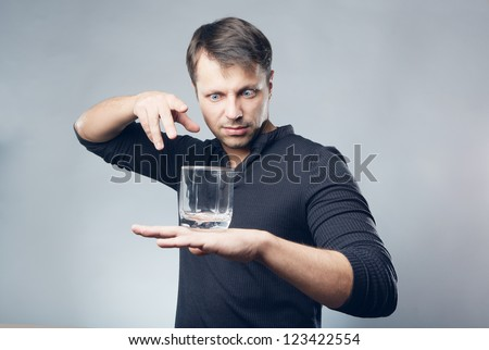 Hypnotist with glass on hand - stock photo
