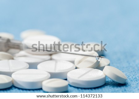 Hypodermic needle with drip medication spilled capsules on blue background