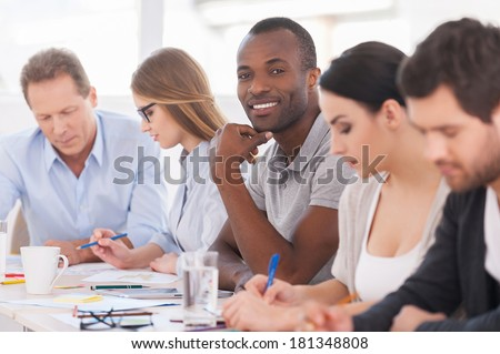 I am a part of strong and creative team. Group of business people sitting in a row at the table while handsome African man looking at camera and smiling - stock photo