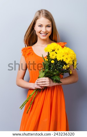 i am a spring. Beautiful young woman in pretty dress holding bouquet of flowers while standing against grey background   - stock photo