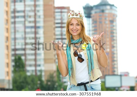 I am a woman! I am the queen! Happy emotional woman with a crown on his head against the background of the city. Woman modern queen. Beautiful young blonde woman points to her crown on her head. - stock photo