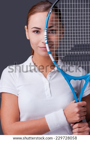 I am in game. Beautiful young women in sports clothes holding tennis racket in front of half of her face and looking at camera while standing against grey background - stock photo