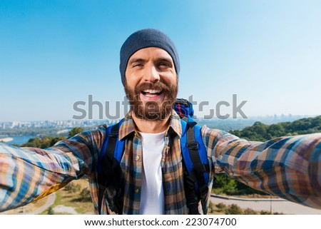 I am in the most beautiful place! Handsome young man carrying backpack and taking a picture of himself  - stock photo