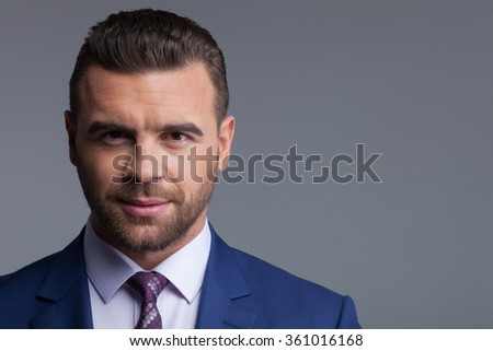 I am ready for meeting. Waist up portrait of handsome businessman is standing in new suit and smiling. He is looking at the camera with confidence. Isolated and copy space in right side