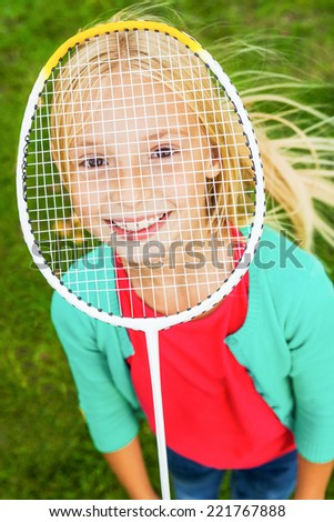 I am ready to play! Top view of cute little girl hiding her face behind badminton racket and smiling while standing on green grass - stock photo