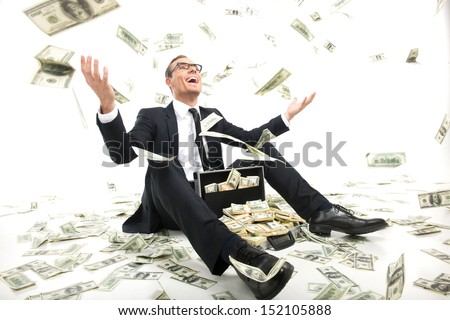 I am rich! Happy young businessman in formalwear throwing money up while sitting near the case full of paper currency - stock photo