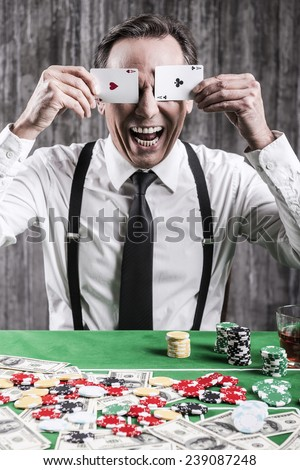 I am so lucky today! Happy senior man in shirt and suspenders sitting at the poker table and covering his eyes with cards  - stock photo