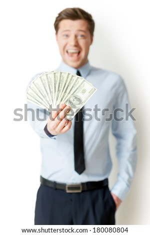 I am so rich! Happy young man in formalwear holding money outstretched and expressing positivity while standing isolated on white