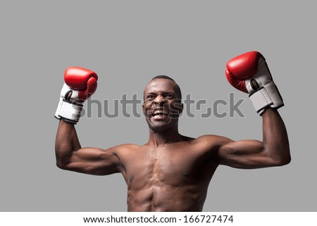 I am the best! Young African boxer raising his hands up and grimacing while standing isolated on grey - stock photo