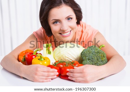 I am vegetarian. Beautiful young woman hugging fresh vegetables laying on the table and smiling