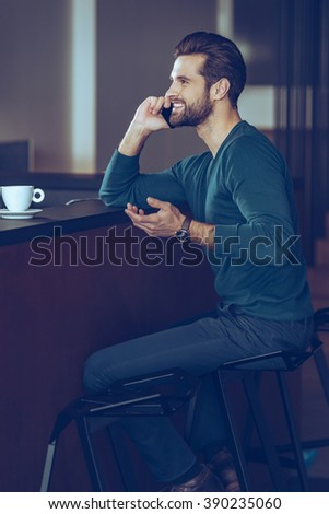 I am waiting for you! Side view of handsome young man talking on mobile phone with smile while sitting at bar counter