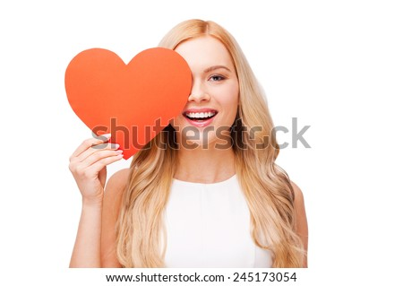 I believe in love! Beautiful young blond hair woman holding heart shaped valentine card in front of her eye and smiling while standing isolated on white - stock photo