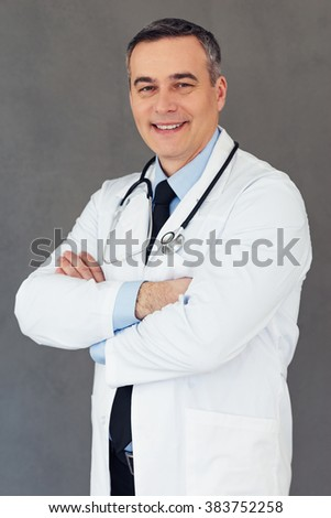 I can cure you! Mature male doctor keeping arms crossed and looking at camera with smile while standing against grey background