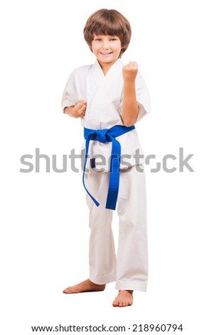 I can defence myself. Full length of little boy in karate uniform standing in karate position while isolated on white - stock photo