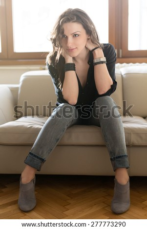 I can go from girly and flirty to edgy and chic. Beautiful young woman posing on the sofa. She is wearing skinny jeans and high heel shoes. - stock photo