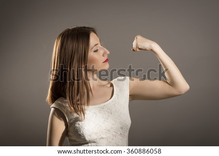"""I can handle any obstacle. Young woman shows her muscles, strength and power concept, studio shoot on gray. """"I can do anything!""""  - stock photo"""