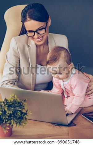 I can help you! Top view of little baby girl using laptop while sitting on office desk with her mother in office - stock photo