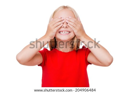 I can see nothing! Cute little girl covering eyes with hands and smiling while standing isolated on white - stock photo