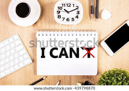 I can, self motivation concept. Crossed out letter 'T so that it reads i can on notepad placed on office desktop with blank smart phone and other items. Mock up - stock photo